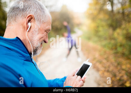 Senior runners in nature, stretching. Man with smartphone with e - Stock Photo