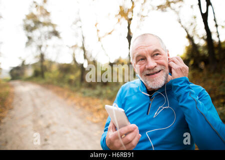 Senior runner in nature with smart phone with earphones. - Stock Photo