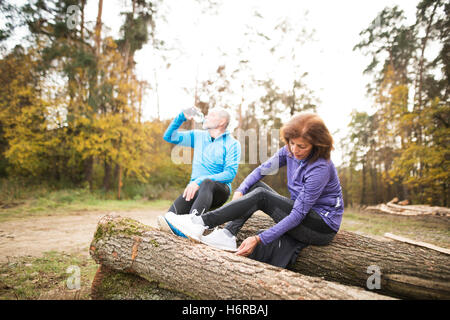 Senior runners sitting on wooden logs, resting, drinking water. - Stock Photo