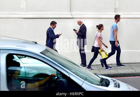 London, England,UK. People using mobile phones, at Hyde Park Corner - Stock Photo
