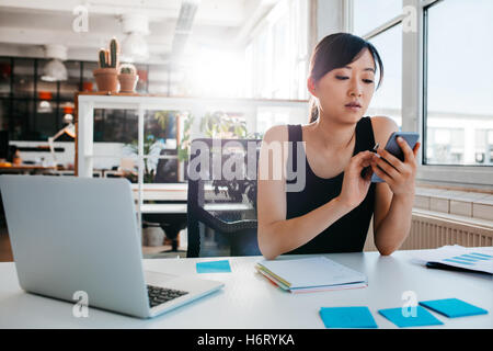 Portrait of young asian woman sitting at her desk with laptop and adhesive notes using mobile phone. Asian businesswoman - Stock Photo