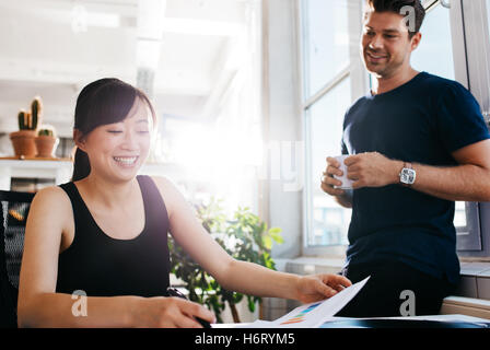 Happy young business partners working together at office. Young people working on new business ideas in office. - Stock Photo