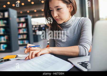 Young woman studying on a book and taking down note while sitting at the library desk. Asian female student preparing - Stock Photo