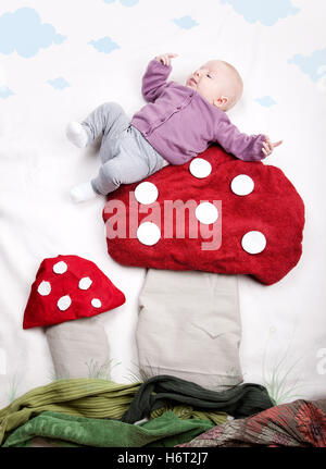 baby on toadstool - Stock Photo