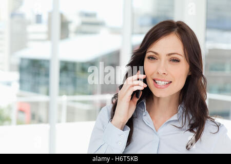 Young smiling manager talking seriously on the cell phone in front of the window - Stock Photo