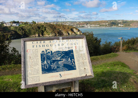 Bilingual tourist information board for historic fort with view to port in Pembrokeshire Coast National Park. Fishguard - Stock Photo