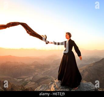 Lone woman in abaya in Al Hajar Mountains of Oman at sunset - Stock Photo