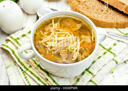Soup with noodles and mushrooms in a white bowl on a napkin, bread on the background light wooden boards - Stock Photo