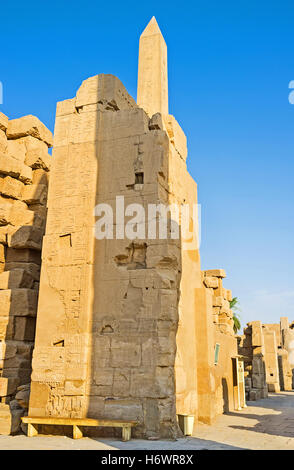 The top of the Hatshepsut Obelisk is seen behind the ruined wall of the ancient temple, Karnak Complex, Luxor, Egypt. - Stock Photo