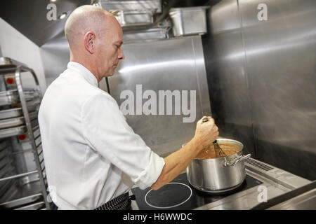 Chef Stirring food in a commercial kitchen in the UK. - Stock Photo