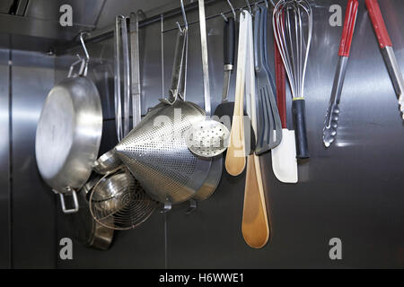 Utensils hanging up in a professional kitchen. - Stock Photo