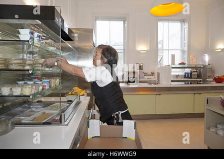 Kitchen worker, replenishing stock and tidying up in a works canteen. - Stock Photo