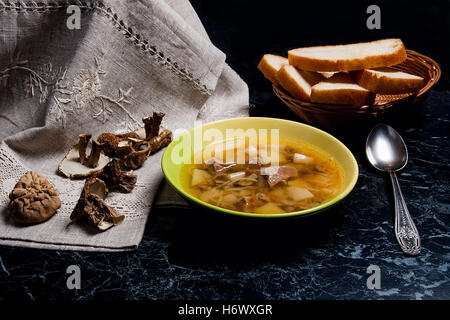 Mushroom soup in green plate with metal spoon on a black stone background. Several dried porcini or white  wild - Stock Photo