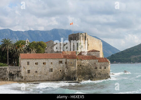 Budva, Montenegro - October 21 2016: national flag of Montenegro flying high above old citadel walls while a storm - Stock Photo