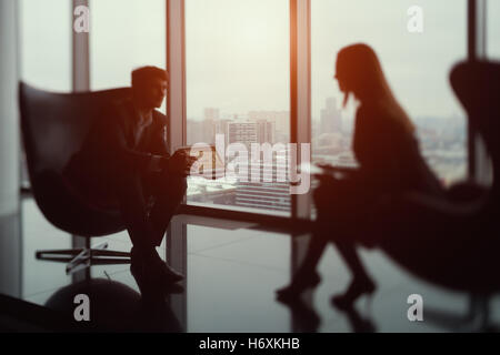 True tilt shift shooting of businessman sitting in front of his female colleague and showing diagrams on his laptop - Stock Photo