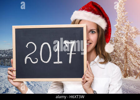 Cute girl in xmas hat with chalkboard - Stock Photo