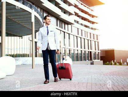 Full length portrait of young executive with a suitcase. - Stock Photo