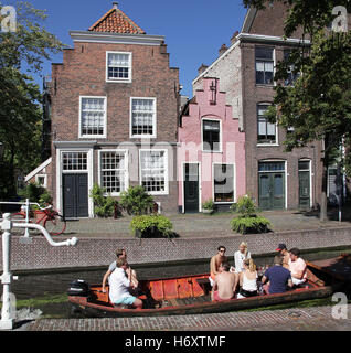 Pink house and Canal in Amsterdam and people in a boat - Stock Photo