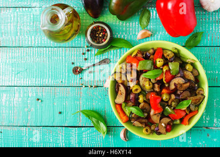 Hot spicy stew eggplant, sweet pepper, olives and capers with basil leaves. Top view - Stock Photo