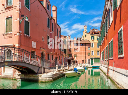 Boats on narrow canal between colorful houses under blue sky in Venice, Italy. - Stock Photo