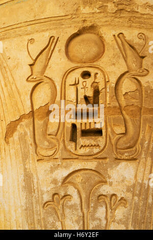 The detail of the stone column in Habu Temple with the carved cobras around the Phraoh, Luxor, Egypt. - Stock Photo
