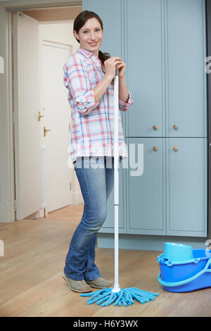 Portrait Of Woman Cleaning Kitchen Floor With Mop - Stock Photo