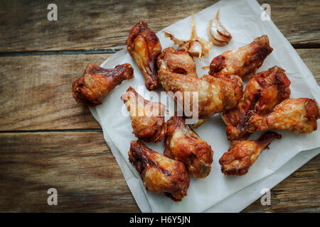 deep fried chicken wings on fryer with garlic - Stock Photo