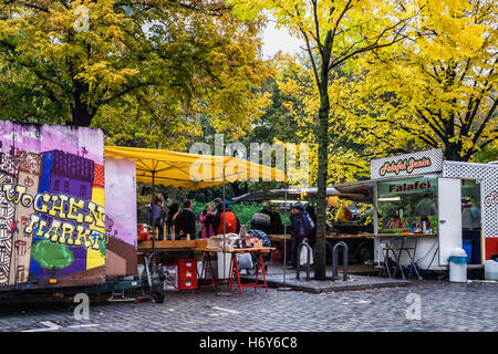 Turkish street market stalls selling fresh produce under yellow autumnal trees in Autumn, Kreuzberg, Berlin - Stock Photo