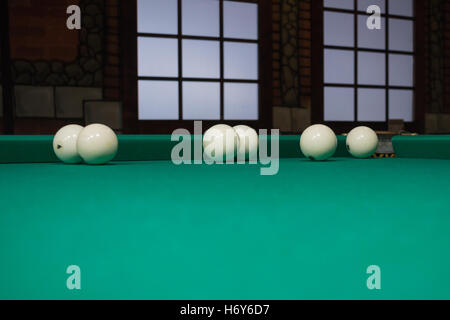 Russian billiards balls on green game table cloth in the middle of game with windows on background - Stock Photo