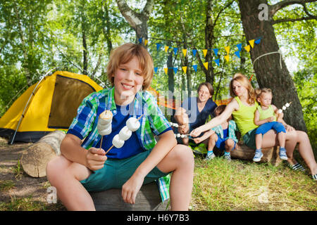Happy boy with grilled marshmallow at the campsite - Stock Photo