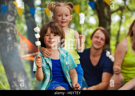 Two cute kids with roasted marshmallow at campsite - Stock Photo