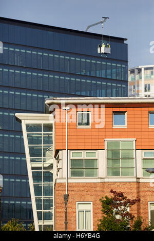 Window cleaner in Basket commercial   Industrial professional cleaners exterior dangling cradle outside lift crane - Stock Photo