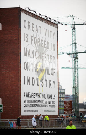 Manchester sign warehouse mural gable   End large massive bee logo creativity is forged in on the anvil of Industry - Stock Photo