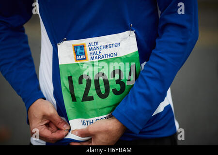 Marathon runner fixing number bib pins   Aldi sponsored event man male father daddy running competition crossing - Stock Photo