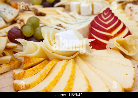 Mixed cheeses on light wooden board. - Stock Photo
