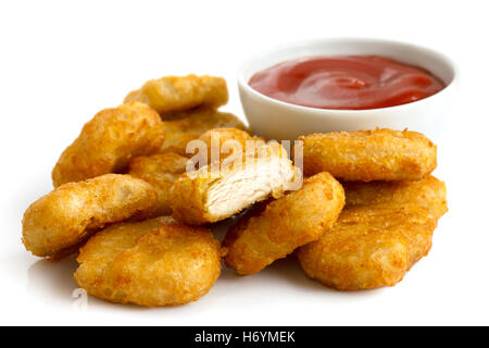 Pile of golden deep-fried battered chicken nuggets with bowl of ketchup, isolated on white. - Stock Photo