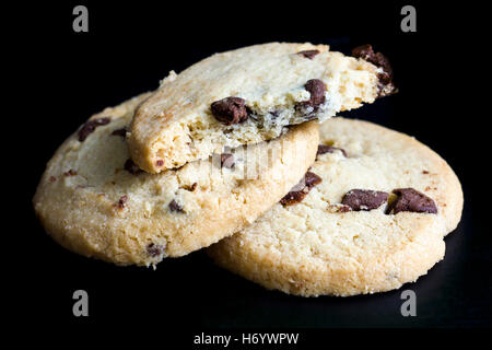 Round chocolate chip shortbread biscuits. On black. - Stock Photo