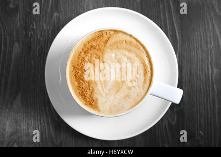Classic foamy cappuccino in color on a black and white grained wood surface - Stock Photo