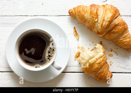 Croissants and coffee on rustic white wood, from above. - Stock Photo