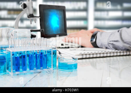 Laboratory tools on white desk and a scientist working on background - Stock Photo