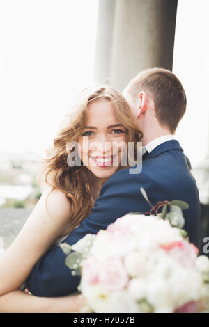 Stylish beautiful wedding couple kissing and hugging on background panoramic view of the old town - Stock Photo