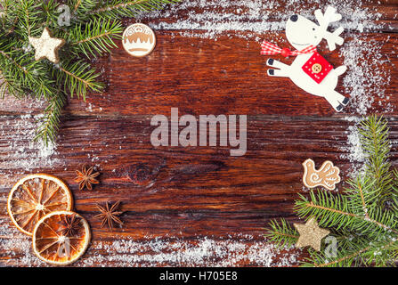 Christmas frame made of fir branches, deer, snow and oranges, laid out on wooden old brown background. Copy space - Stock Photo