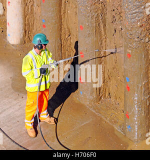 Man working in full health & safety gear new motorway widening retaining wall construction high pressure water jet - Stock Photo