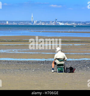 Older man sitting alone on Ryde Isle of Wight UK beach at low tide sketching views of the Solent towards distant - Stock Photo