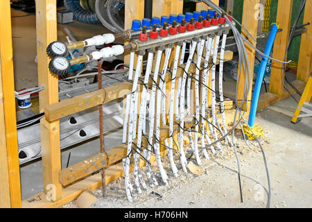 Interior of new UK energy efficient Passive House under construction showing underfloor heating pipes await join - Stock Photo