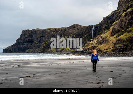 A woman walks across the empty beach at Talisker Bay on the Isle of Skye, Scotland. - Stock Photo