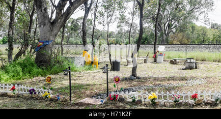 An Elaborate Roadside Memorial Carved out of the bush where two people were killed in a traffic crash. - Stock Photo