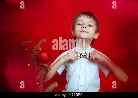 Boy in white shirt correcting a bow tie dressed up in Christmas tree - Stock Photo