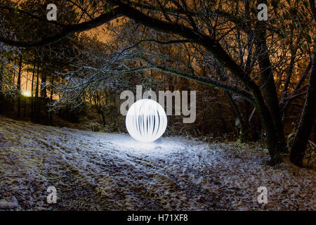 Futuristic glowing sphere on a background of a beautiful winter landscape in full moon - Stock Photo