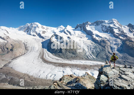 Hiker looking over Gorner Glacier and Monte Rosa from Gornergrat. Zermatt, Pennine Alps, Valais, Switzerland. - Stock Photo